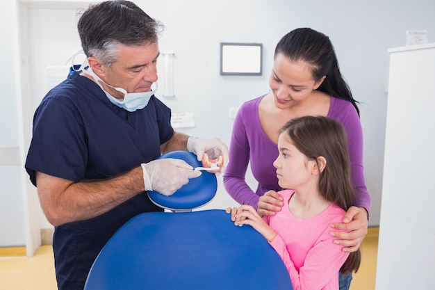 Zahnarzt, der jungem patienten und ihrer mutter erklärt, wie zahnbürste verwenden