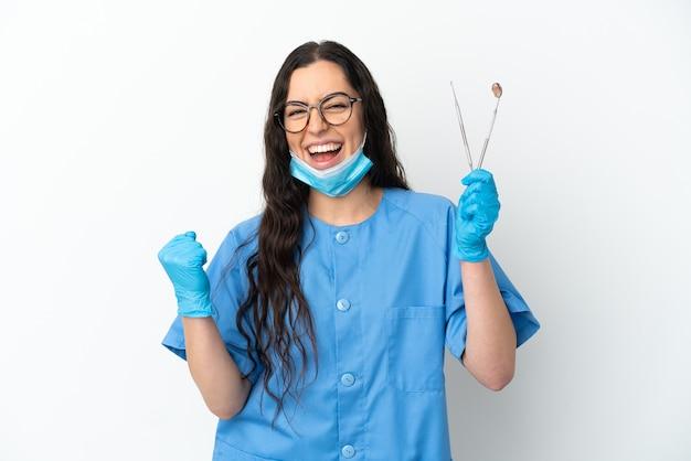 Zahnarzt der jungen frau, die werkzeuge lokalisiert auf weißer wand hält, die einen sieg feiert