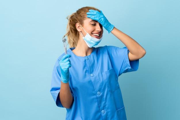 Zahnarzt der jungen frau, die werkzeuge über lokalisiertem lachendem blauem hintergrund hält