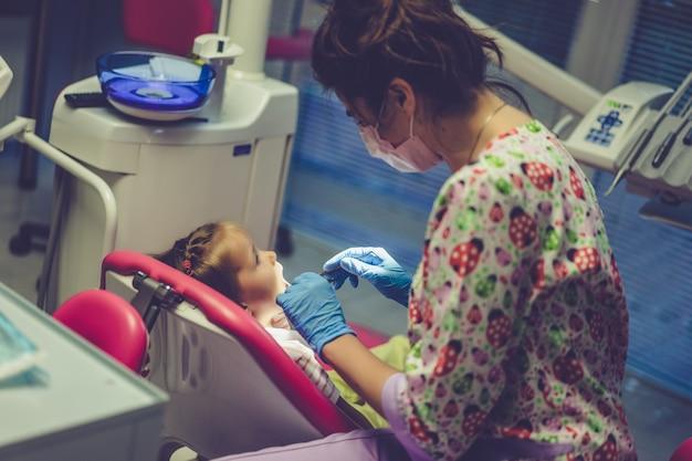 zahnarzt der kleines mädchen in ihrem büro überprüft