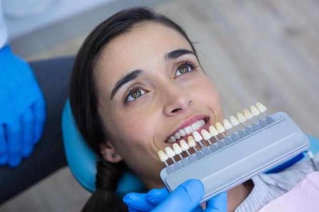 Zahnarzt, der medizinische ausrüstung hält, während frau untersucht