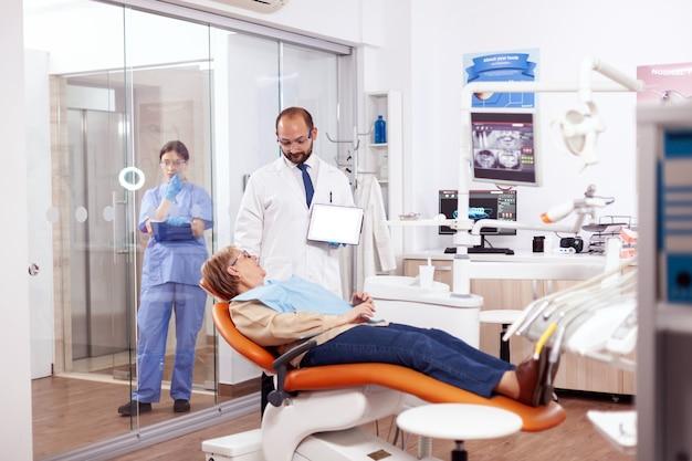 Zahnarzt, der mit älterer frau im kabinett bespricht, das tablette-pc mit verfügbarem kopienraum hält. medizinische zahnpflege mit digitalem gerät mit patientenradiographie auf tablet-pc in der nähe des aufstehenden patienten.