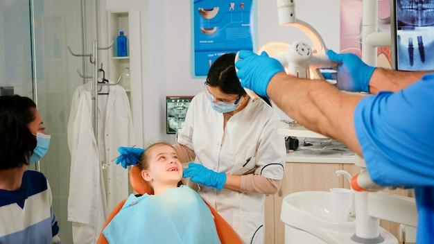 Zahnarzt, der mit spiegelzahngesundheit des patienten des kleinen mädchens überprüft. krankenschwester zündet die lampe an, arzt spricht mit kind, das auf einem stomatologischen stuhl sitzt, sich auf die reinigung der zähne vorbereitet, die betroffene masse behandelt treating
