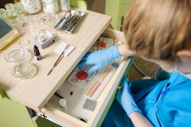 Zahnarzt, der nach zahnmedizinischem werkzeug im stomatologiebüro sucht