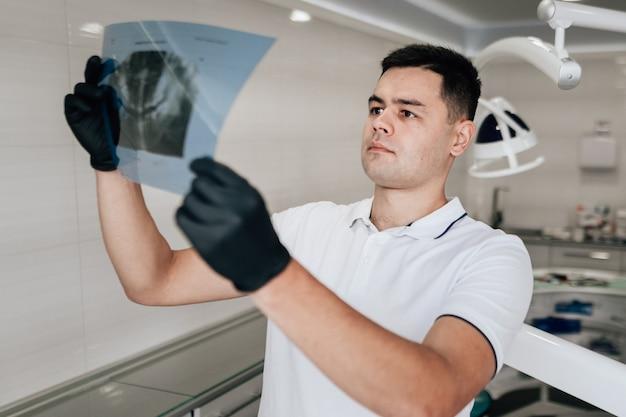 Zahnarzt, der radiographie im büro betrachtet