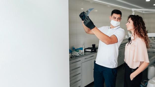 Zahnarzt, der radiographie mit patienten- und kopienraum hält