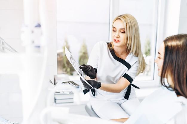 Zahnarzt, der röntgenstrahl für den patienten zeigt und plan der behandlung erklärt.