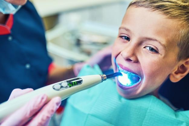 Zahnarzt, der seine zähne behandelt und die höhle in einer modernen klinik füllt