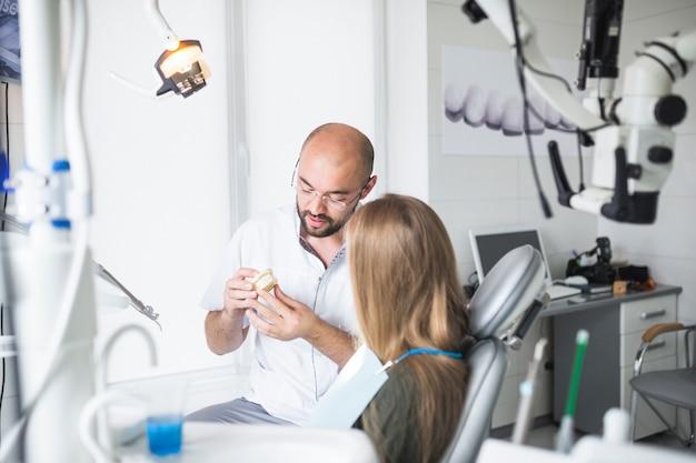 Zahnarzt, der seinem weiblichen patienten zahnmedizinischen kiefer zeigt