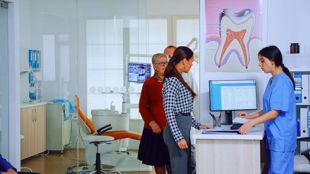 Zahnarzt, der senioren in beratungszimmer einlädt, während die krankenschwester dem patientenformular zum ausfüllen angibt, auf dem stuhl im wartebereich zu sitzen. zeitlupenaufnahme überfüllte professionelle kieferorthopädie