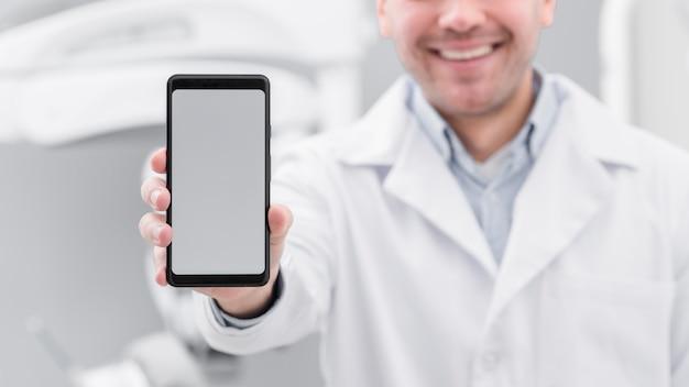 Zahnarzt, der smartphone darstellt