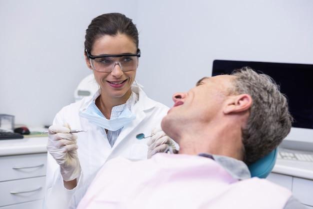 Zahnarzt, der werkzeug beim betrachten des mannes in der klinik hält