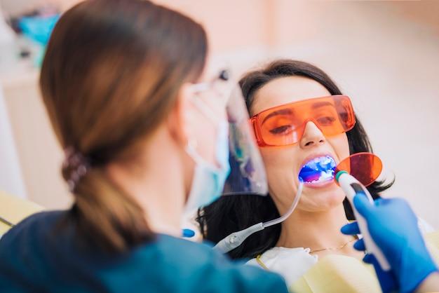 Zahnarzt, der zähne des patienten mit ultraviolettem weiß wird