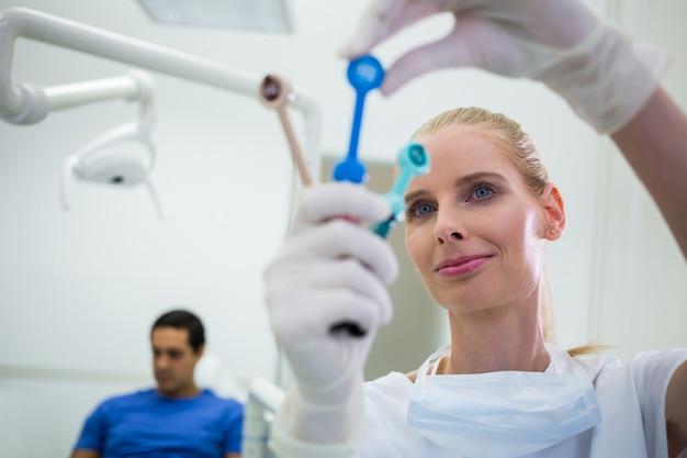 Zahnarzt, der zahnärztliche werkzeuge betrachtet