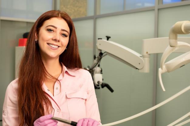 Zahnarzt doktor in der zahnarztpraxis. junge und schöne ärztin in der medizinischen kleidung und in den schutzbrillen, hält ein professionelles zahnmedizinisches werkzeug in ihren händen. lächelnd.