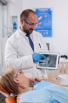 Zahnarzt im zahnmedizinischen kabinett, der die zahndiagnose auf dem digitalen gerät erklärt, das aufsteht. medizinischer zahnpfleger, der patientenradiographie auf tablet-pc in der nähe des aufstehenden patienten hält.