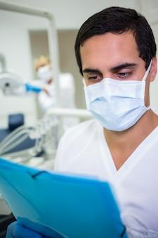 Zahnarzt in der chirurgischen maske, die eine medizinische akte betrachtet