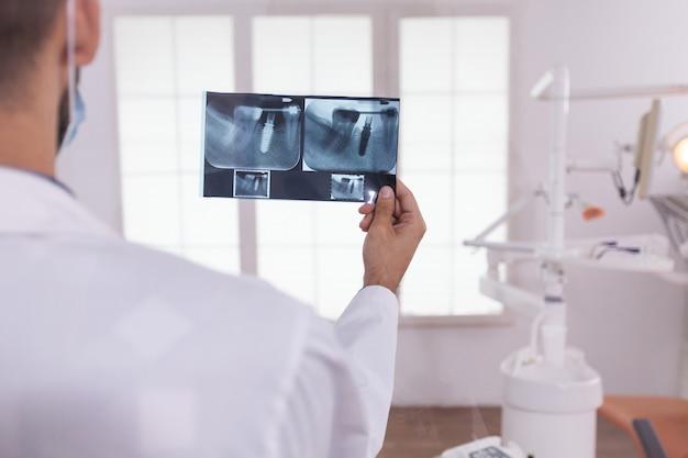 Zahnarzt-mann-arzt, der kieferorthopädische zähne medizinische radiographie analysiert, die im büroraum des stomatologie-krankenhauses arbeitet. im hintergrund leerer kieferorthopäde, der sich auf die zahngesundheitschirurgie vorbereitet