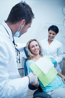 Zahnarzt mit dem assistenten, der hände mit frau rüttelt