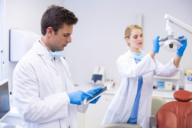 Zahnarzt mit digitalem tablet, während sein kollege das zahnlicht anpasst