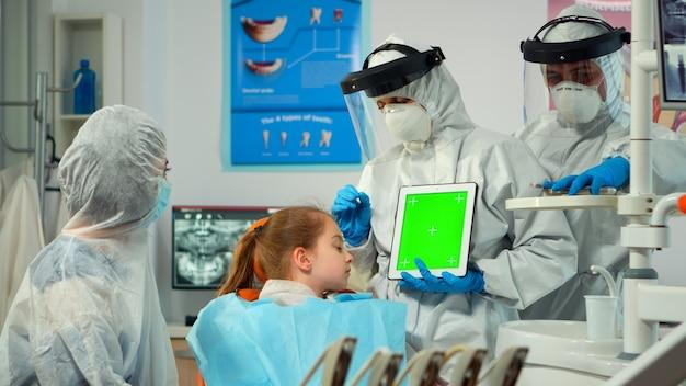Zahnarzt mit gesichtsschutz, der auf greenscreen-display zeigt, der während der coronavirus-epidemie mit einem kind mit zahnschmerzen spricht. erklären der verwendung eines monitors mit chroma-key-izolation-chroma-pc-key-mockup-anzeige