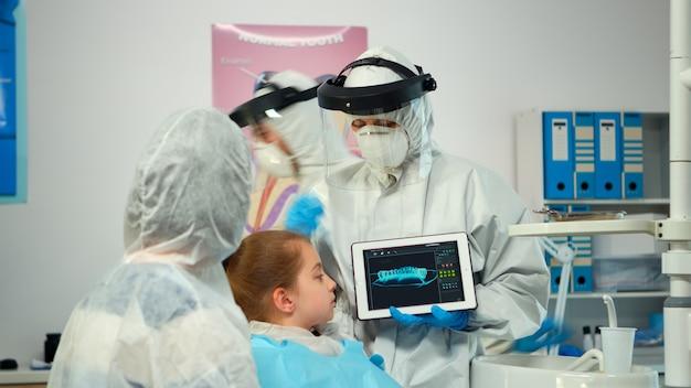 Zahnarzt mit ppe-anzug, der auf den digitalen bildschirm zeigt und der mutter des mädchenpatienten röntgen erklärt. ärzteteam und patienten mit gesichtsschutzoverall, maske, handschuhen und röntgenaufnahmen mit notebook
