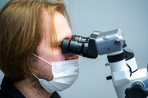 Zahnarzt mit schutzmaske und handschuhen repariert den zahn eines kunden bei moderner ambulanter behandlung mit mikroskop. mundpflege.