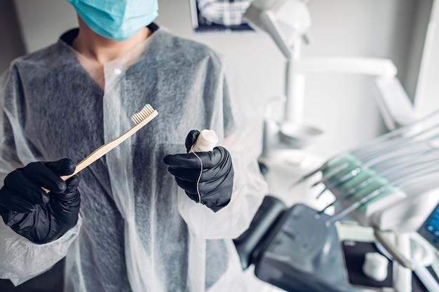 Zahnarzt mit zahnbürste und zahnseide in der klinik