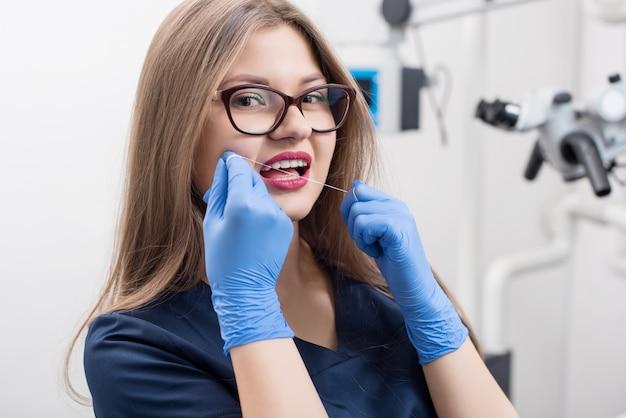 Zahnarzt mit zahnseide