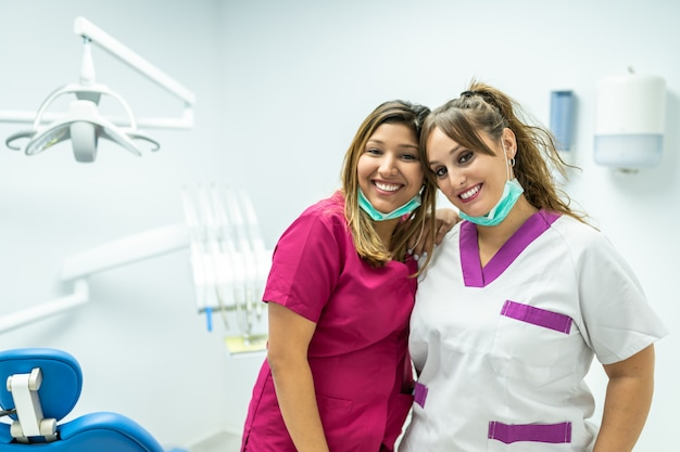 Zahnarzt mit zwei frauen, der zur kamera lächelt