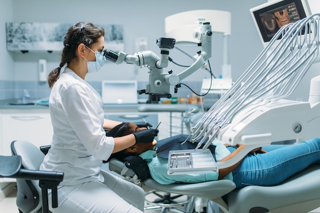 Zahnarzt operiert patientin, besuch in der zahnklinik. frau im zahnarztschrank, stomatologie, zahnpflege