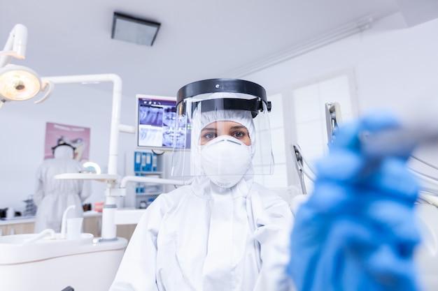 Zahnarzt pov, der die zahnhygiene des patienten mit einem bohrer überprüft, um die zahnhöhle zu reparieren. stomatolog trägt schutzausrüstung gegen coronavirus während der gesundheitsprüfung des patienten.
