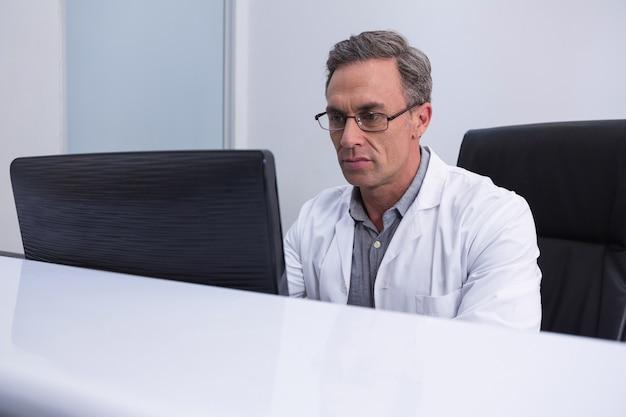Zahnarzt sitzt am computer am tisch