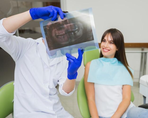 Zahnarzt und frau, die radiographie betrachten