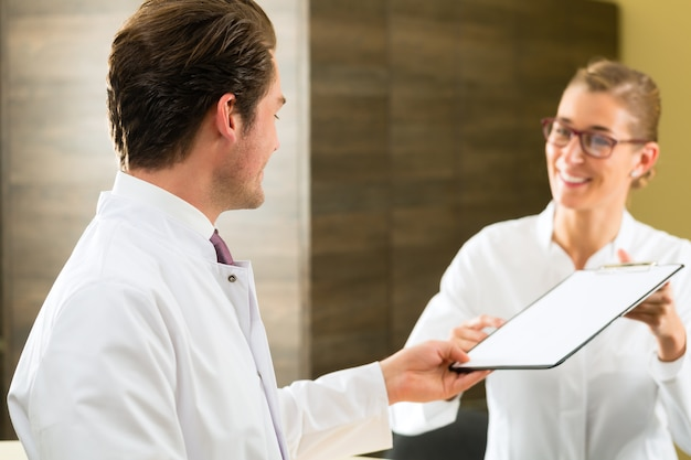 Zahnarzt und krankenschwester mit zwischenablageklinik