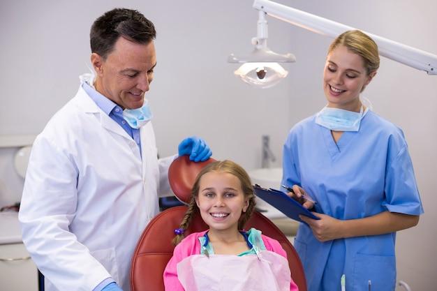 Zahnarzt und krankenschwester stehen neben jungen patienten