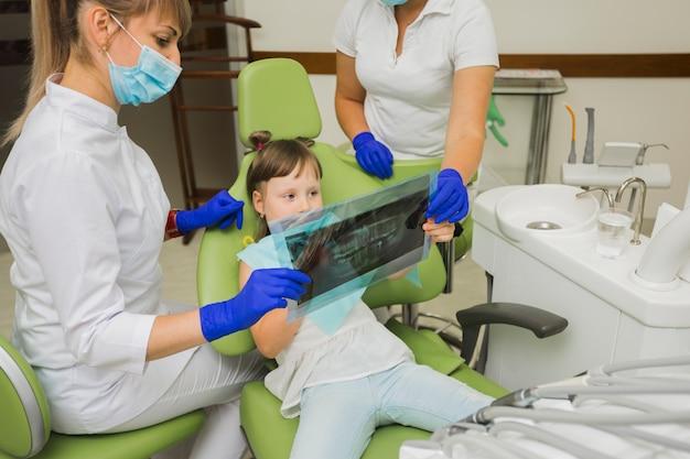Zahnarzt- und mädchenpatient, der radiographie betrachtet