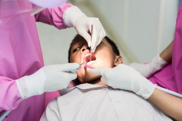 Zahnarzt- und zahnarztassistent zähne für kinder an der hygiene überprüfend.
