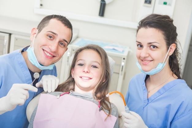 Zahnarzt- und zahnarzthelferporträt mit jungem patienten