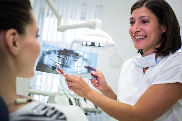 Zahnarzt zeigt ihrer patientin röntgen