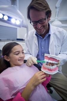 Zahnarzt zeigt jungen patienten, wie man zähne putzt