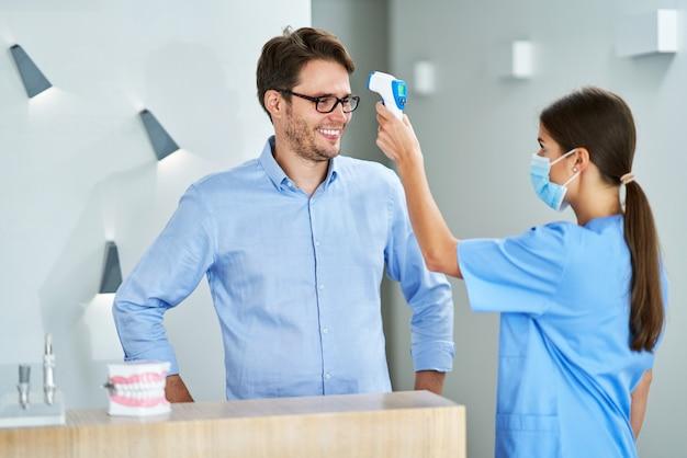 Zahnarztassistent, der aufgrund von covid-19-verfahren die temperatur an den kunden misst