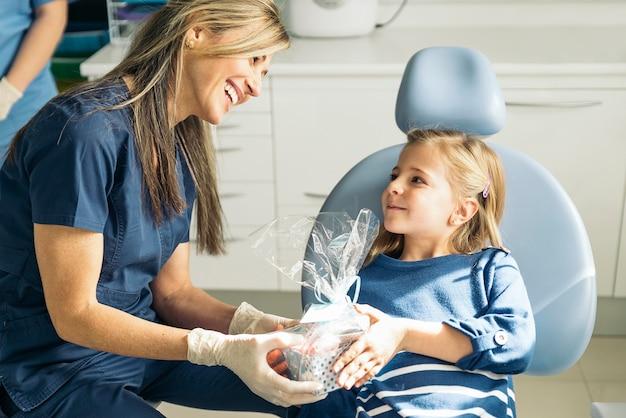 Zahnarztdoktor, der einem mädchen ein geschenk gibt. medizinisches konzept
