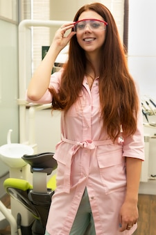Zahnarztdoktor steht an vor dem hintergrund des zahnmedizinischen büros. junge und schöne ärztin in der medizinischen kleidung und in den schutzbrillen. in die kamera lächeln