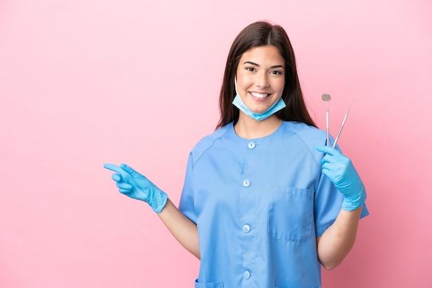 Zahnarztfrau, die werkzeuge lokalisiert auf rosa hintergrund hält und mit dem finger zur seite zeigt