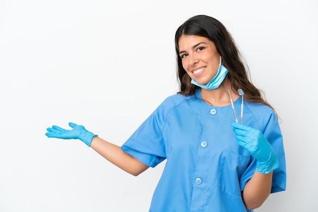 Zahnarztfrau, die werkzeuge über isoliertem weißem hintergrund hält und die hände zur seite ausstreckt, um einzuladen, zu kommen
