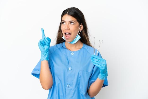 Zahnarztfrau, die werkzeuge über isoliertem weißem hintergrund hält und eine idee denkt, die mit dem finger nach oben zeigt