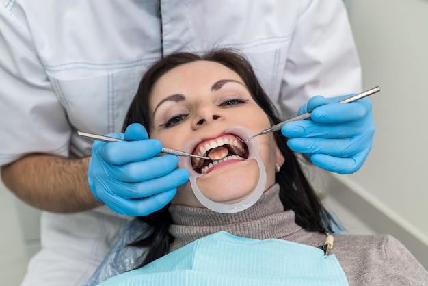 Zahnarzthände mit instrumenten und patientengesichtsnahaufnahme
