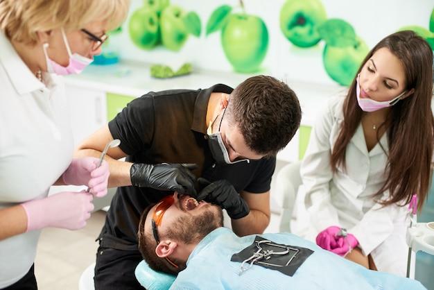 Zahnarzthelfer in anwesenheit eines arztes bereitet den patienten auf die entfernung des zahns vor