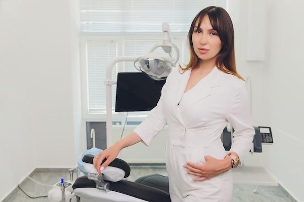 Zahnarzthelferin im untersuchungsraum lächelndes junges zahnarztporträt der frau.